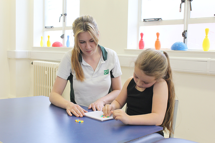Child completing fine motor tasks with therapist